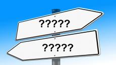 An image of two signs pointing in opposite directions each bearing question marks