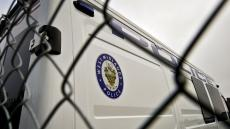 An image of the logo on the side of a West Midlands Police van, as seen through a fence