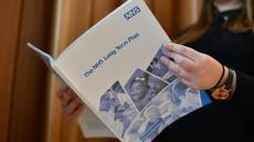 An image of a woman reading the NHS Long Term Plan document