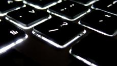 A close up image of a keyboard centred on the forward slash and question mark key