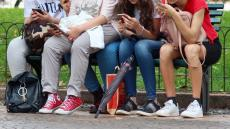 An image of four young women on a bench using mobile phones. Their faces are unseen.