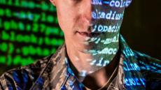 An image of the face of a military professional with computer code superimposed on their face