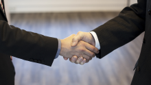 Close-up image of a handshake between two men in suits