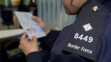 Border Force official checking a passport