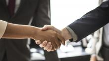 Image of a man and woman shaking hands in a business environment