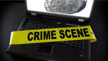 Laptop with a crime scene banner over the keyboard