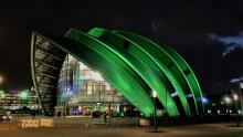 An image of the exterior of the SEC Centre in SEGlasgow illuminated green