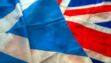 A close-up image of sections of a Scottish Saltire flag and UK Union flag lying next to one another