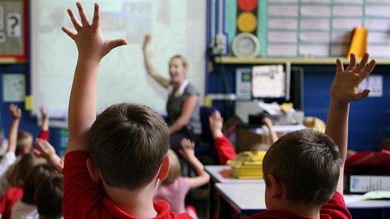 Two school children raise their hands in a classroom