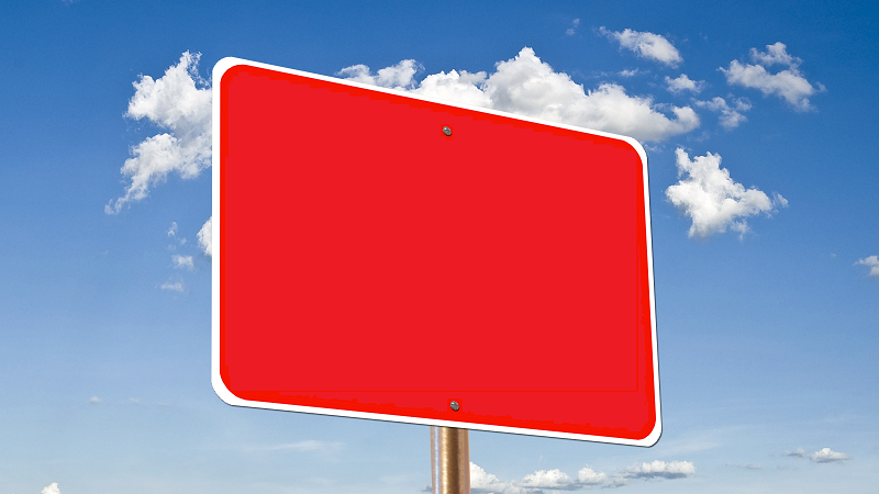 A blank red sign in front of white clouds and blue sky