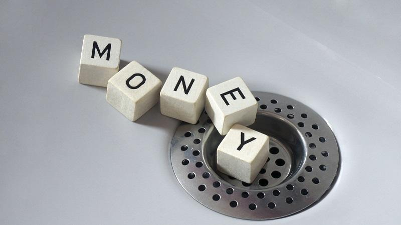 A picture of dice spelling out the word 'money' going down a drain