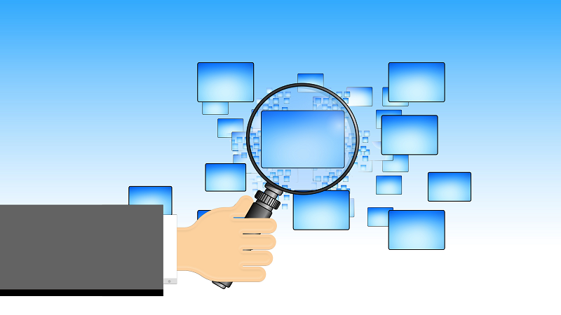 Image of a magnifying glass over computer screens