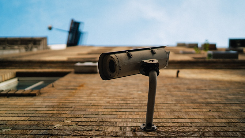 A view from below of a surveillance camera attached to a wall