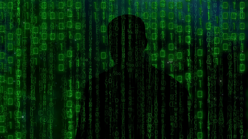 Image of a shadowy figure with a background of zeroes and ones