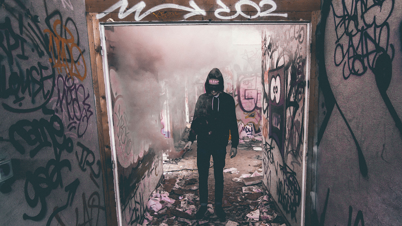 Image of a youth with a flare surrounded by graffiti