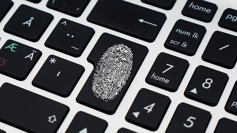 Image of a thumbprint on the 'Enter' key of a keyboard, implying a biometric identity service