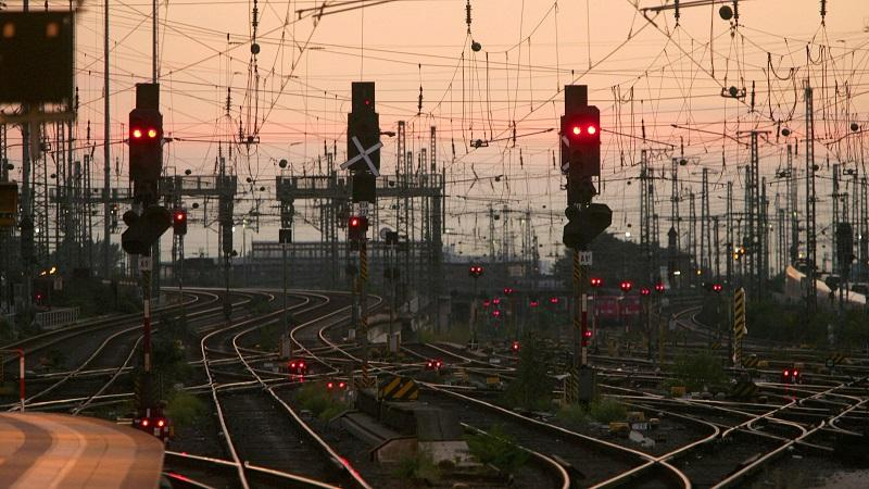 An image of railway tracks and signals in the German city of Frankfurt, set against an early evening sky