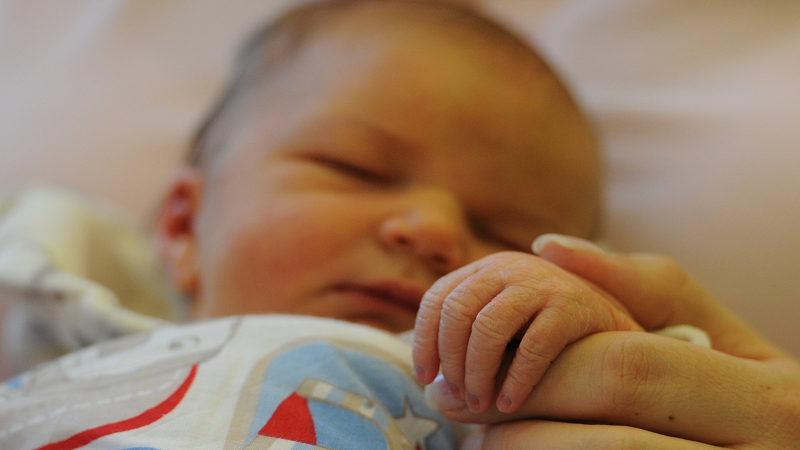 Image of a newborn baby holding its mother's finger