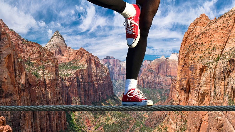 An image of a woman in trainers balancing on a steel wire above a canyon