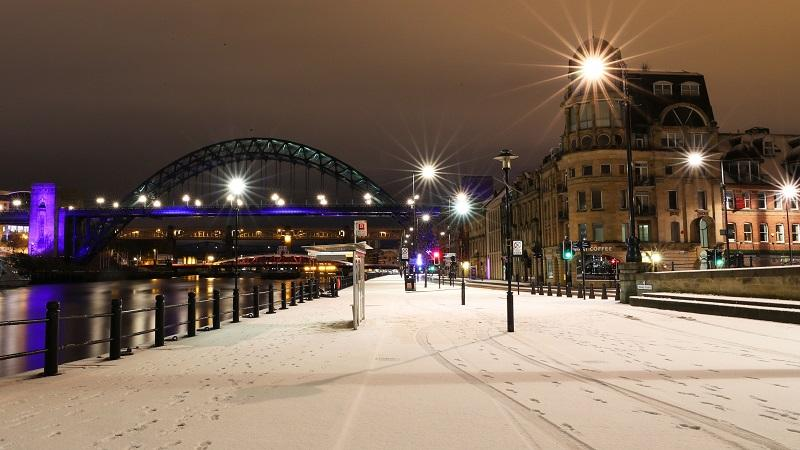 An image of Tyne Bridge in Newcastle at night, with a snow-covered riverside path in foreground