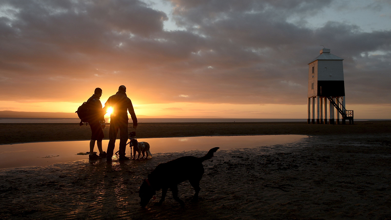 Image of sunset over beach at Burnham-On-Sea, with dog walkers walking near the lighthouse