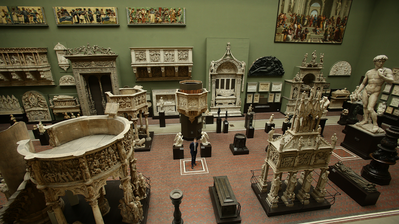 An image of an exhibition room at the Victoria and Albert Museum in London, with museum director Tristram Hunt standing in the middle of the floor among exhibits