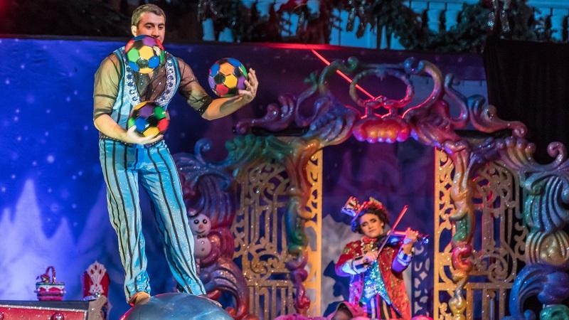 An image of a circus performer juggling three balls while balancing on a large ball, while a violinist plays in the background