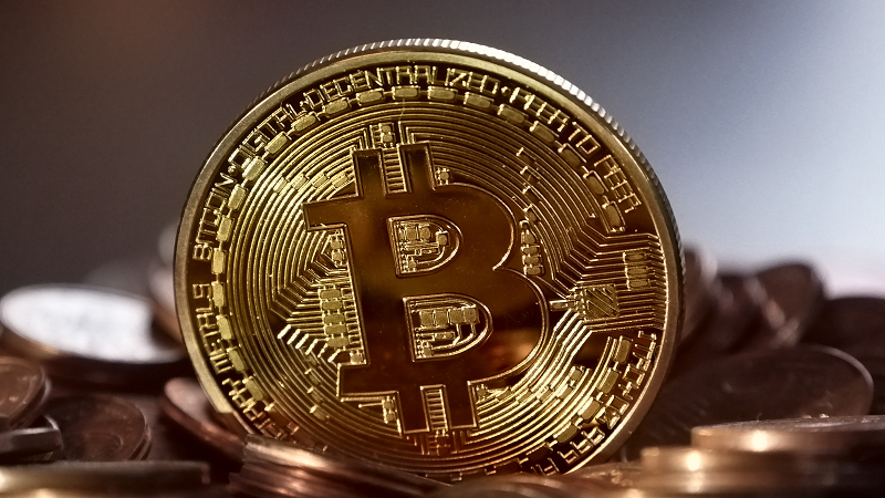 Image of a coin bearing the Bitcoin logo propped up among a pile of other coins