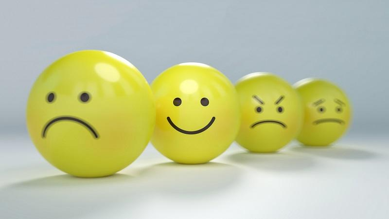 Image of four balls depicting emoticon-style faces denoting sadness, happiness, anger, and confusion