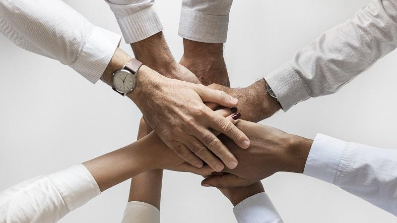 An image of seven people joining hands in the middle of a group