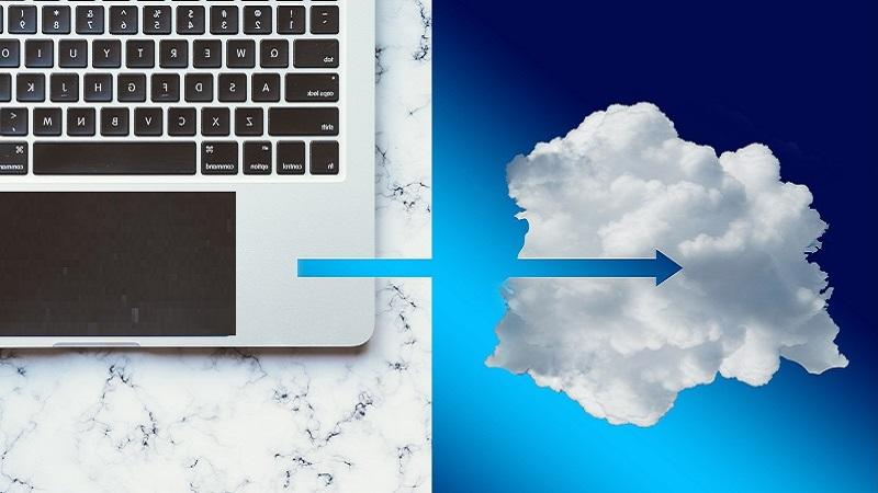 An image of an arrow pointing between a laptop and a cloud