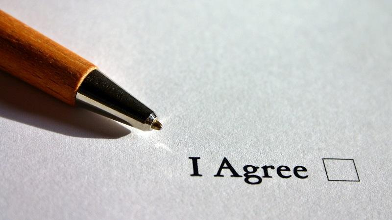 An image of a pen and an as-yet unticked tick box with the words 'I Agree'