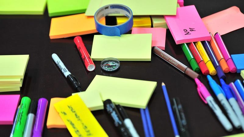 An image of sticky notes, pens, pencils, a compass and some sticky tape all laid out haphazardly on a table