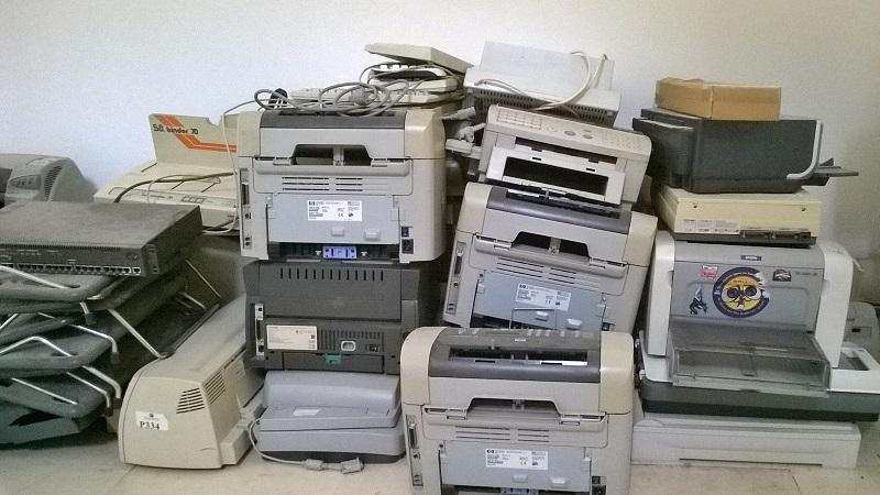 An image of a pile of old printers left to gather dust on an office floor