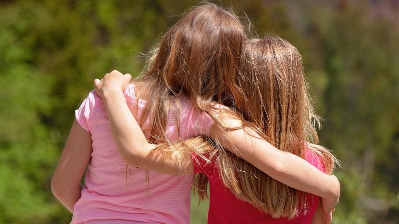 An image of two young girls with their arms around each other