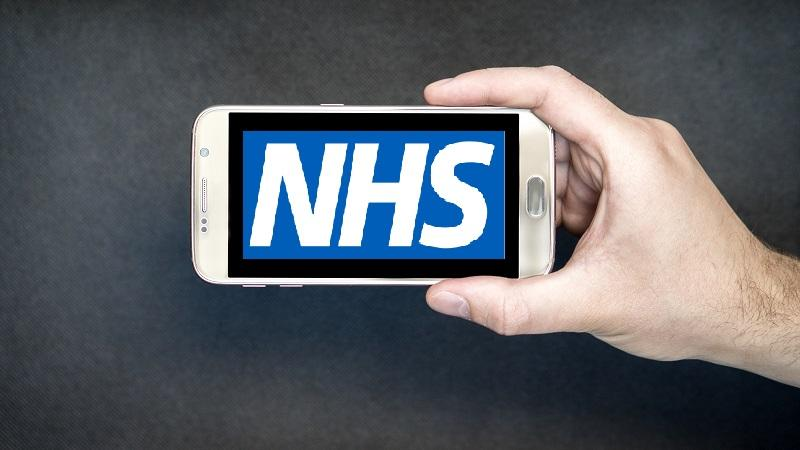 An image of the NHS logo displayed on a smartphone screen held up by a hand