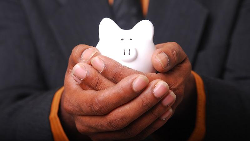 A close-up image of a man holding a piggy bank in his hands in a protective way