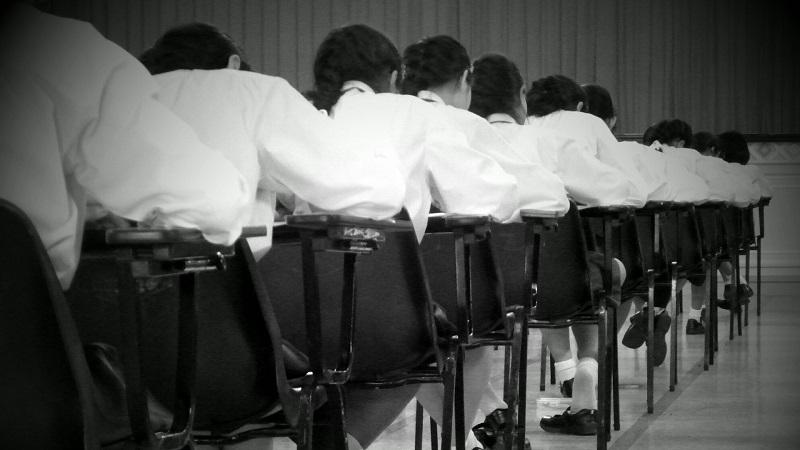 An image of a row of students sat in an exam hall taking an exam