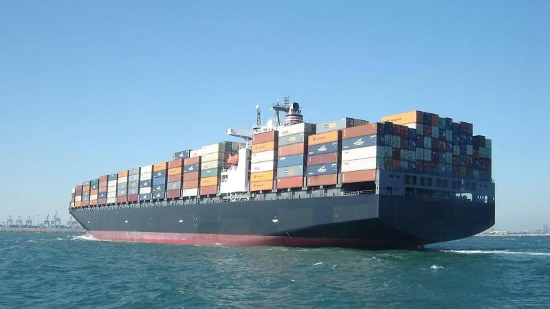 An image of a cargo ship travelling with lots of shipping containers