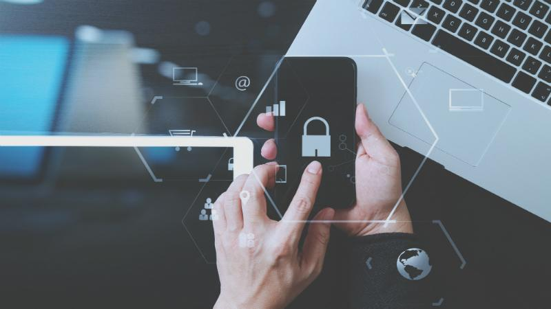 Businessman hand working with VR screen padlock icon mobile phone on computer background