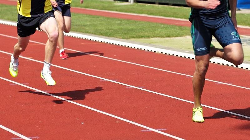 A close-up image of two runners racing on a track