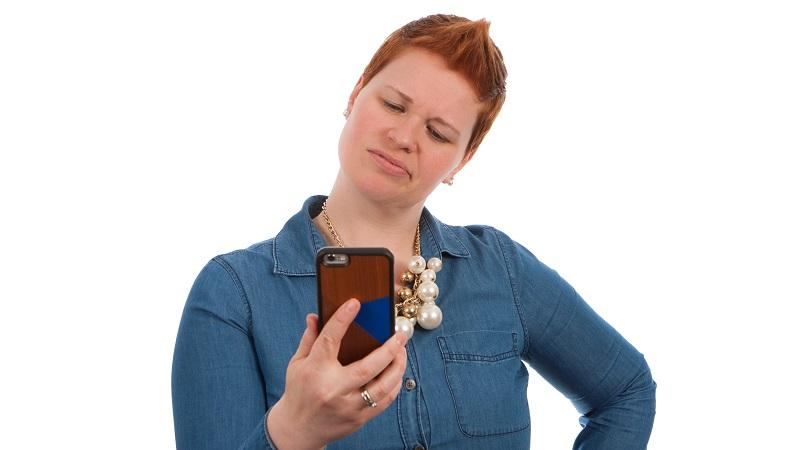 An image of a woman looking frustratedly at a mobile phone