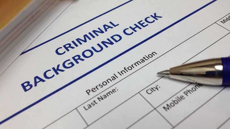 An image of a pen sat on top of a form headed 'criminal background check'