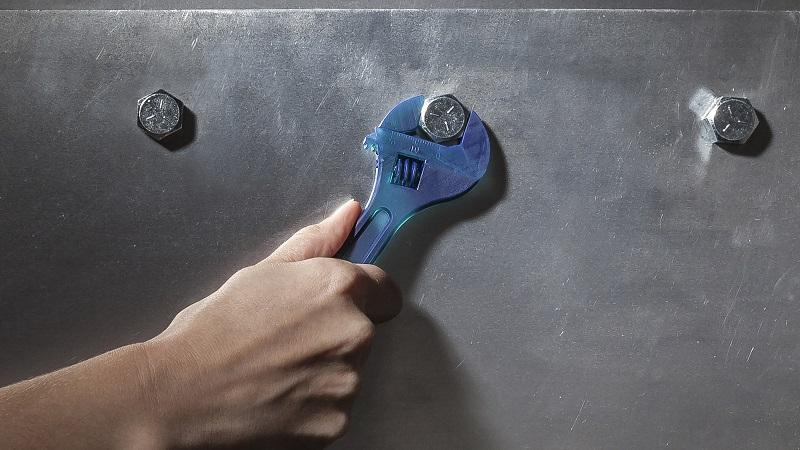 An image of a spanner being used to tighten a nut