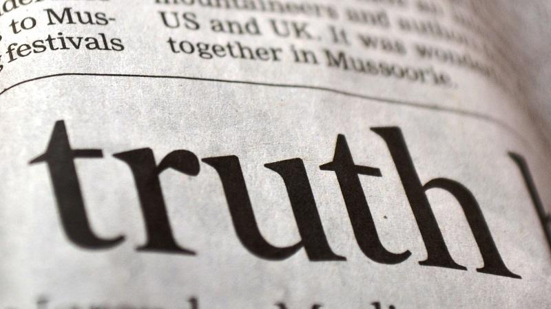 A close-up image of a newspaper headline displaying the word 'truth'