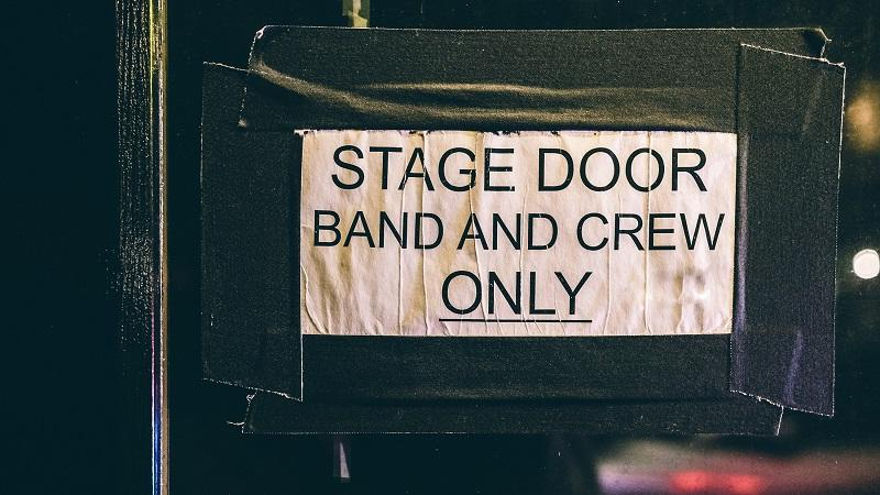 A close-up image of a handmade sign stating 'Stage door - band and crew only'