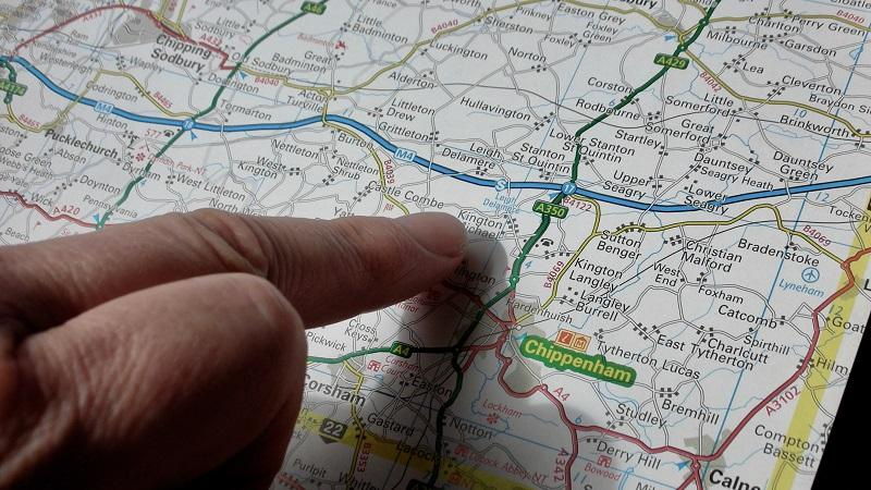 A close image of a finger pointing at something on a UK road atlas