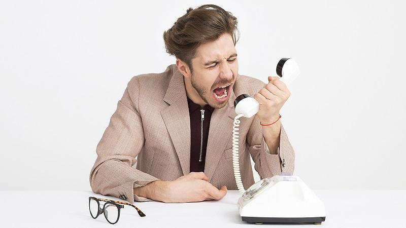An image of an angry man shouting into phone