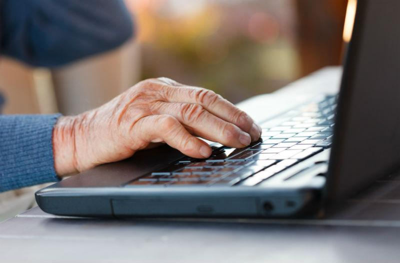 picture of an elderly person's hand operating a laptop