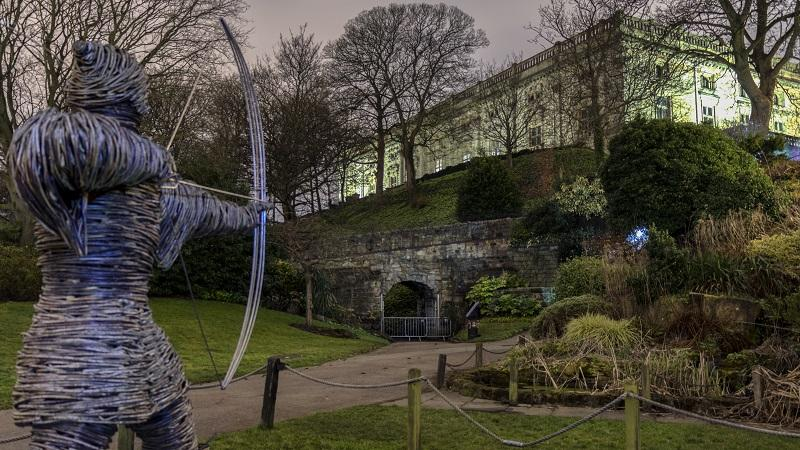 A statue of Robin Hood points a bow and arrow at the exterior of Nottingham Castle